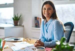 A woman smiling and working in her office.